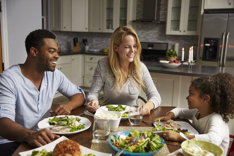 Ragazza ed i suoi genitori della corsa mista che pranzano nella loro cucina immagini stock