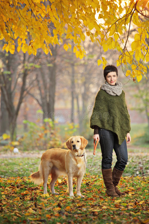 Ragazza ed il suo cane che camminano in autunno immagine stock libera da diritti