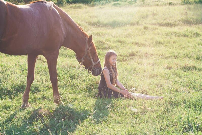 Ragazza ed il suo cavallo sul campo soleggiato immagini stock