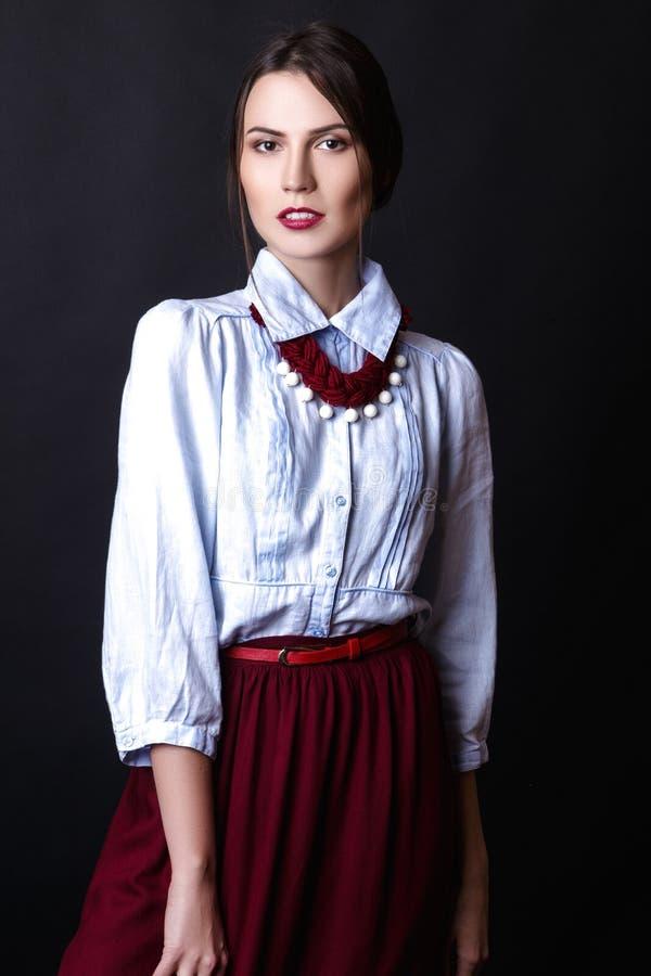 Ragazza elegante in blusa del denim e gonna rossa in studio su fondo bianco immagini stock libere da diritti