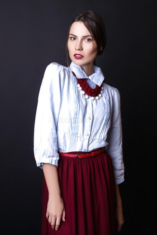 Ragazza elegante in blusa del denim e gonna rossa in studio su fondo bianco fotografie stock