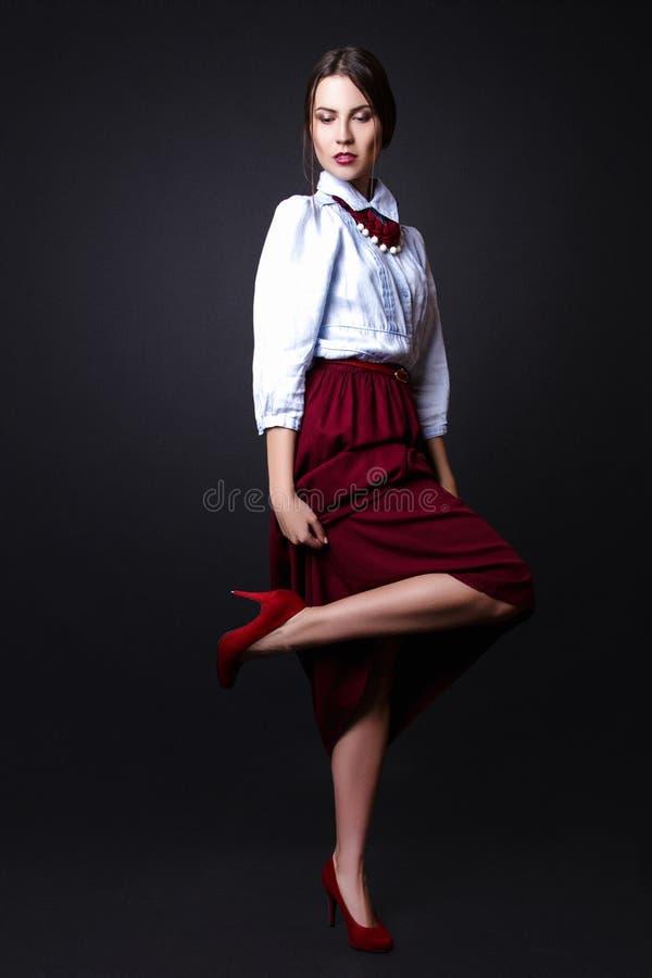 Ragazza elegante in blusa del denim e gonna rossa in studio su fondo bianco fotografia stock