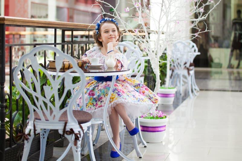 Ragazza elegante del bambino in un tè bevente del vestito floreale fotografie stock