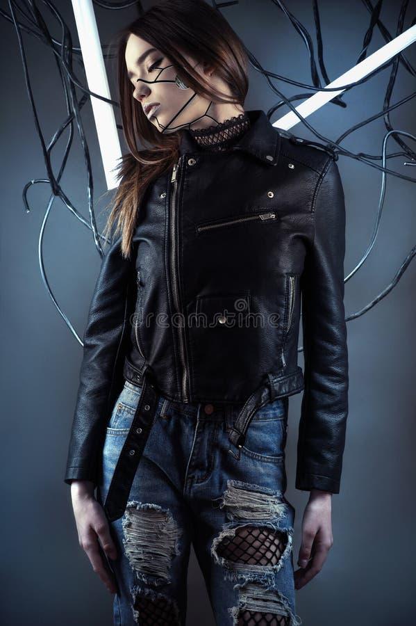 Ragazza elegante del robot in cavi nel Cyberpunk di stile in bomber e jeans strappati fotografie stock libere da diritti