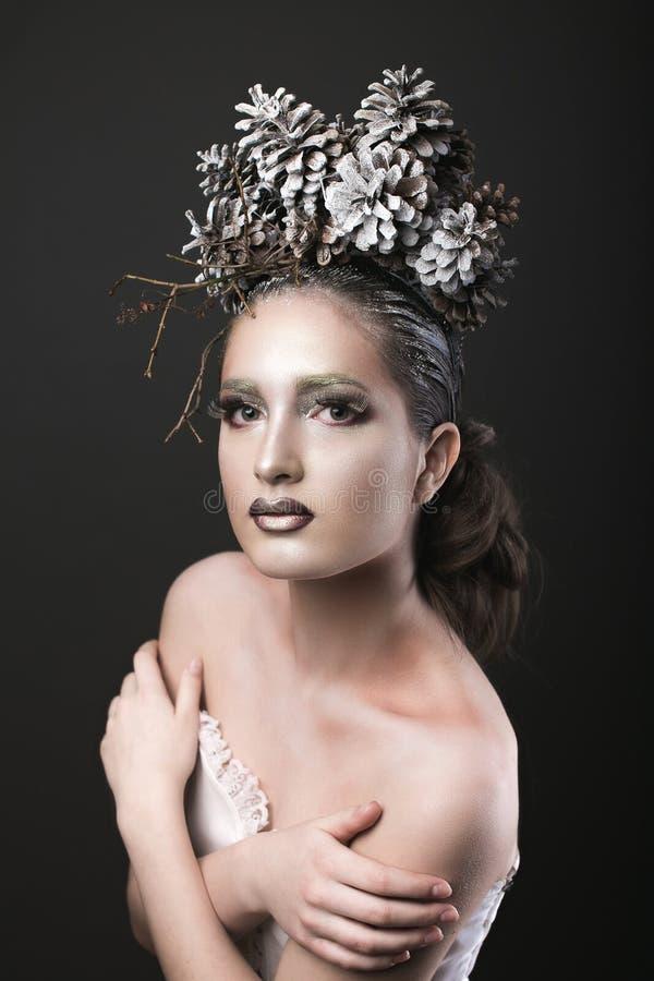 Ragazza elegante nella corona del nuovo anno delle pigne fotografia stock