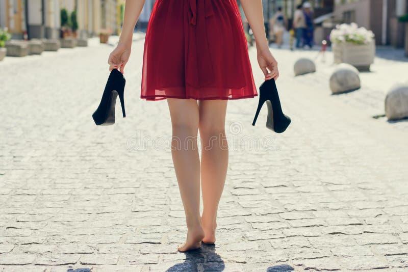 Ragazza elegante in vestito rosso con i tacchi alti in mani, walkin fotografie stock libere da diritti