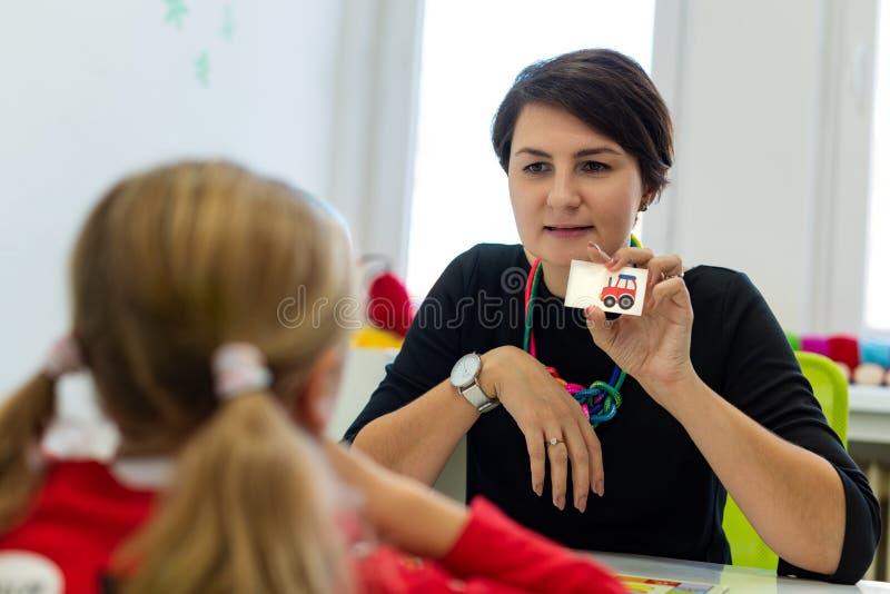 Ragazza elementare di età nella sessione di terapia occupazionale del bambino che fa gli esercizi allegri con il suo terapista fotografia stock libera da diritti