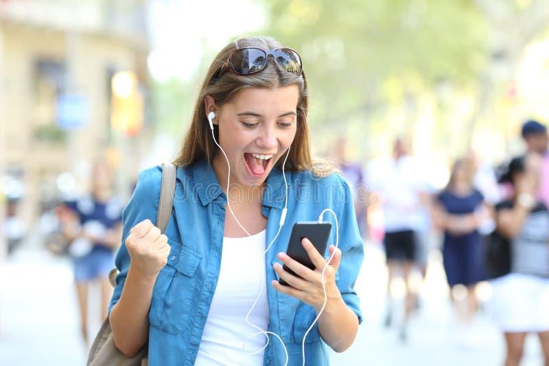 Ragazza emozionante che ascolta la musica online all'aperto fotografia stock libera da diritti