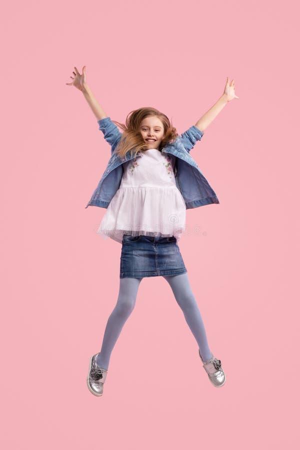 Ragazza emozionante che salta con la mano sollevata fotografia stock