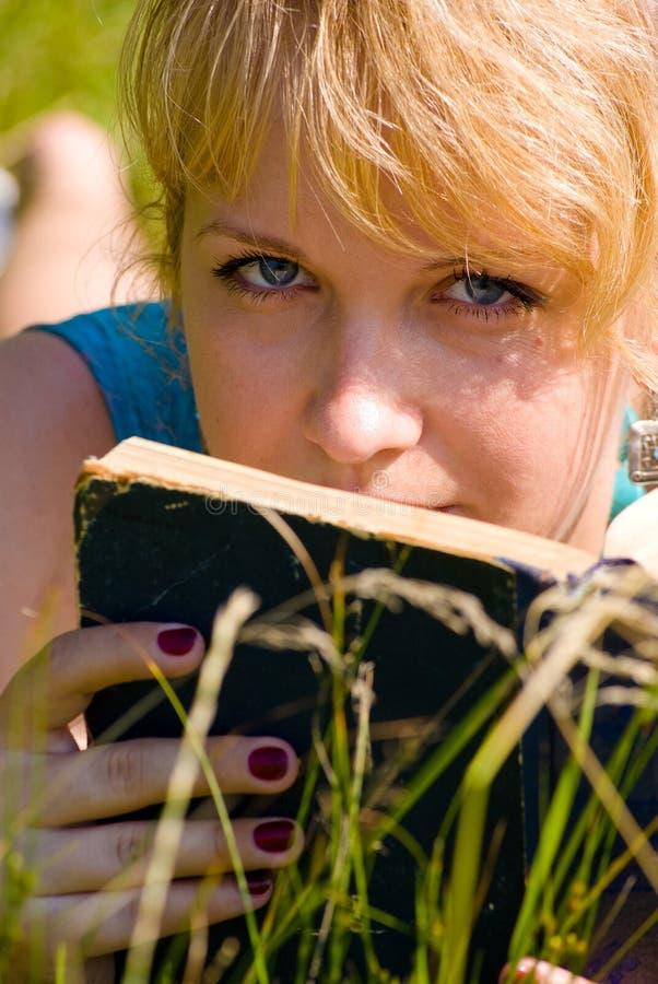 Ragazza in erba con il libro fotografia stock
