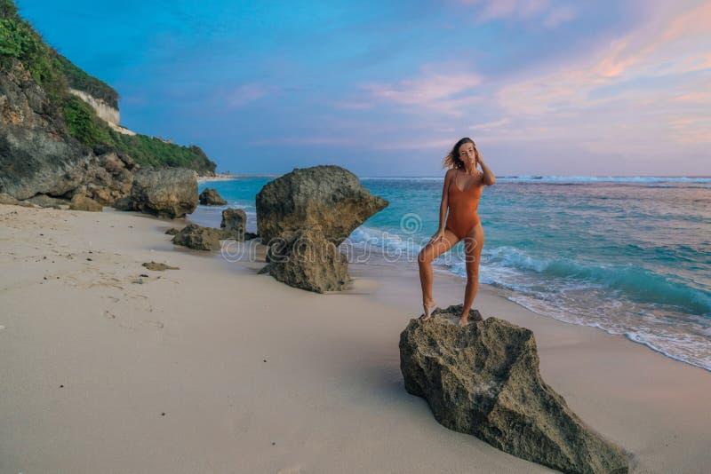 Ragazza esile nella condizione del costume da bagno sulla grande pietra al fondo selvaggio della spiaggia di bello tramonto fotografia stock