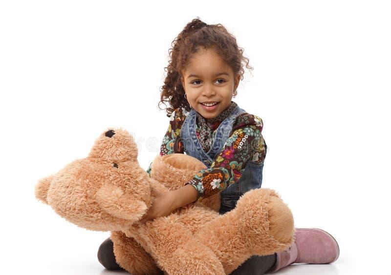 Ragazza etnica sveglia che gioca con sorridere dell'orso della peluche immagine stock