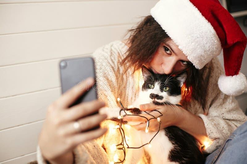 Ragazza felice alla moda in cappello di Santa che prende selfie con il gatto sveglio alle luci di natale su fondo dei regali Giov fotografie stock