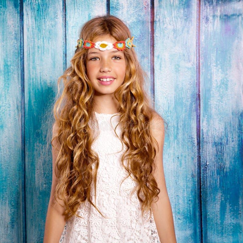 Ragazza felice bionda dei bambini di hippy che sorride sul legno blu fotografia stock