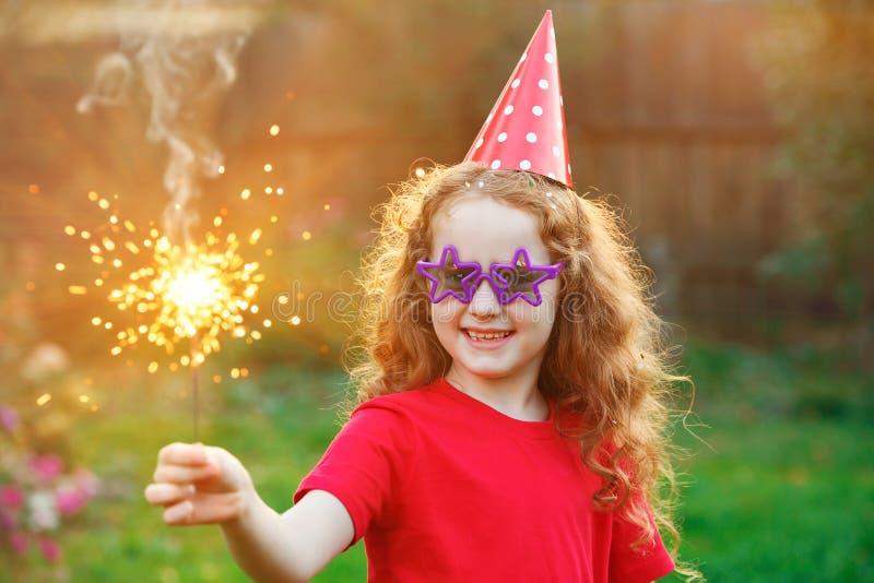 Ragazza felice in cappello del partito con la stella filante bruciante in sua mano fotografia stock libera da diritti