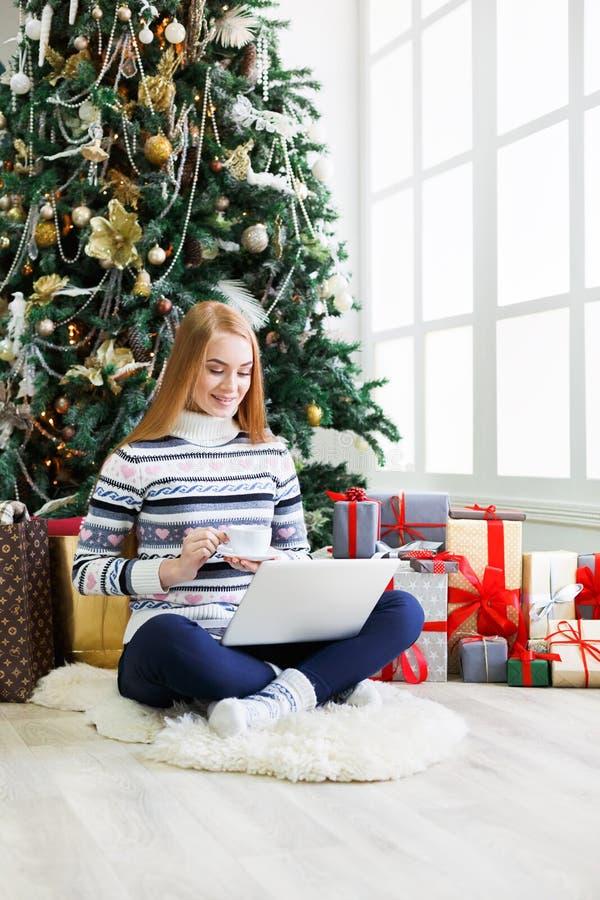 Ragazza felice in cappello di Santa che chiacchiera online sul computer portatile fotografie stock