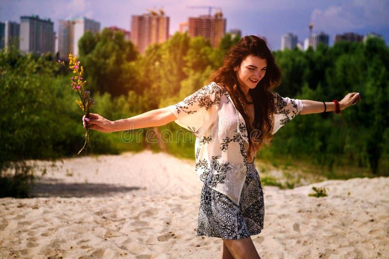 Ragazza felice che balla nei raggi di bello tramonto nel parco bella ragazza nell'ambito dei raggi di un tramonto caldo immagini stock