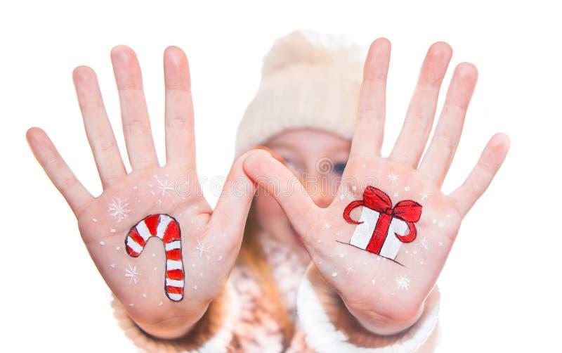 Ragazza felice che dimostra i simboli dipinti di Natale sulle sue mani Il Babbo Natale, renna immagini stock
