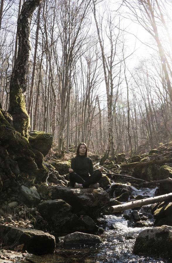 Ragazza felice che fa il loto di posa di yoga che si siede in una roccia su un fiume che medita nella foresta con luce solare fotografia stock libera da diritti