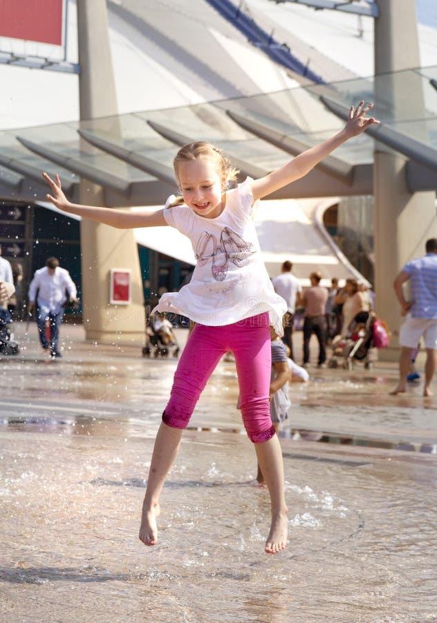 Ragazza felice che gioca e che salta in fontana immagini stock libere da diritti