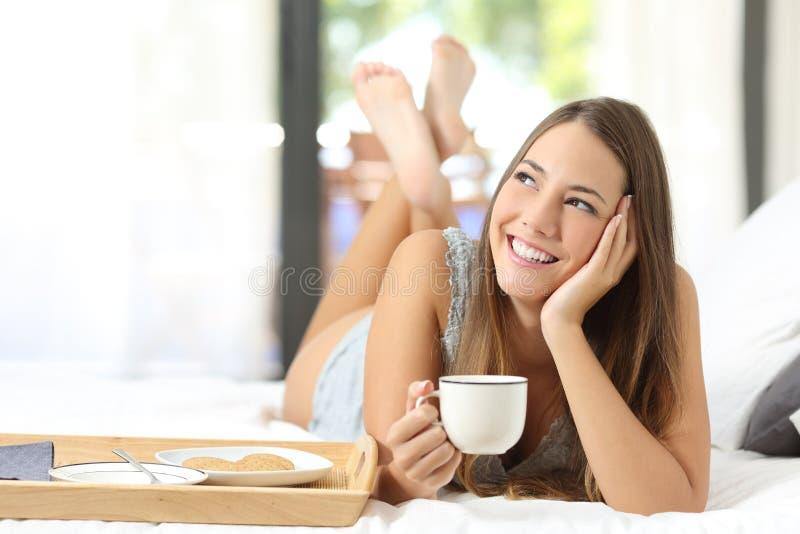 Ragazza felice che mangia prima colazione che tiene una tazza di caffè fotografia stock libera da diritti