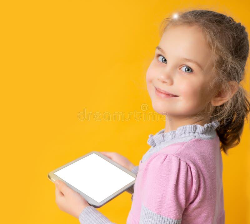 Ragazza felice che per mezzo della compressa, isolata su fondo arancio fotografie stock libere da diritti