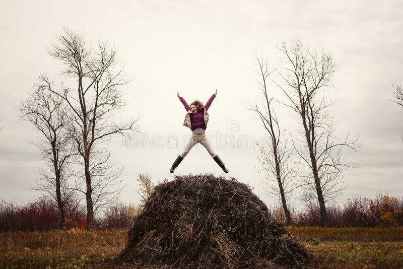 Ragazza felice che salta sul fieno in autunno immagine stock
