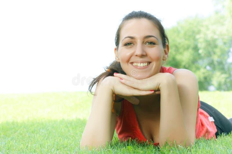 Ragazza felice che si distende sull'erba verde immagini stock libere da diritti