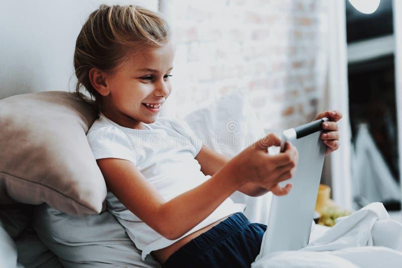 Ragazza felice che si siede con la compressa digitale a disposizione immagine stock
