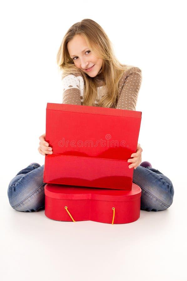Ragazza felice che si siede vicino ai contenitori di regalo fotografia stock libera da diritti