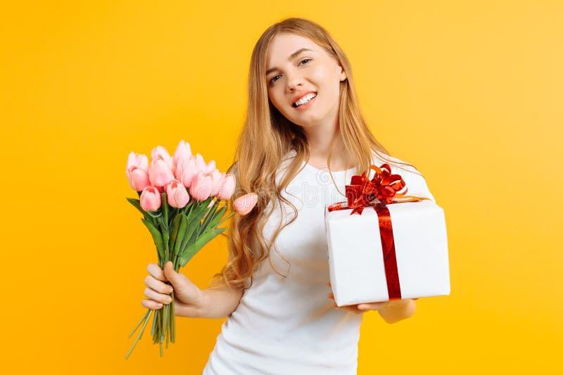 Ragazza felice che tiene un mazzo di bei fiori e di un contenitore di regalo su un fondo giallo immagine stock libera da diritti