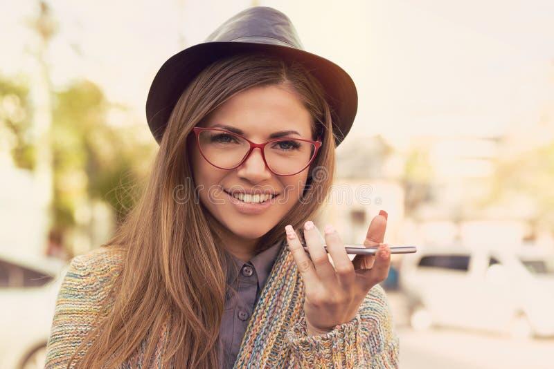 Ragazza felice che usando una funzione di riconoscimento della voce dello Smart Phone sulla linea che cammina su una via fotografie stock