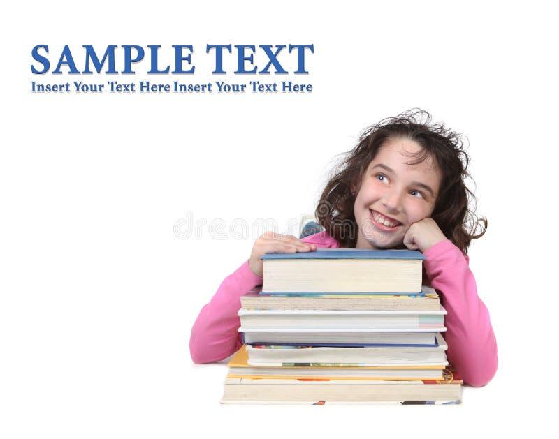Ragazza felice con i libri di banco che osservano in su immagine stock