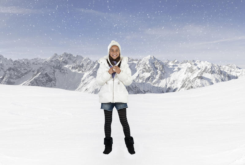 Ragazza felice con il cappello di inverno nelle montagne immagine stock