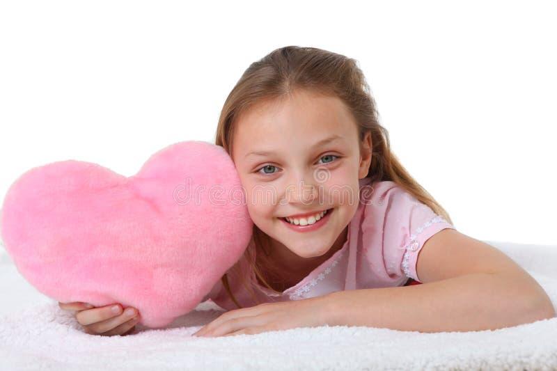 Ragazza felice con il cuscino rosa del cuore fotografie stock libere da diritti