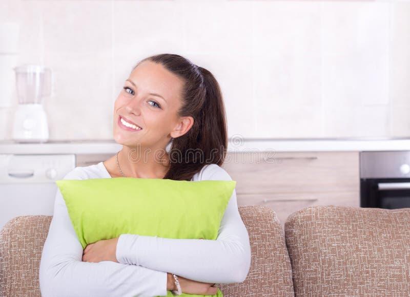 Ragazza felice con il cuscino sul sofà fotografie stock
