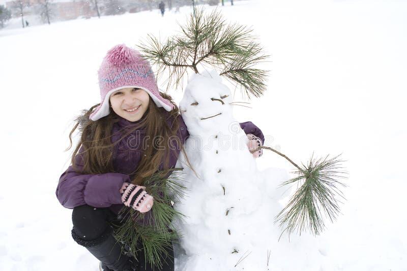 Ragazza felice con il suo pupazzo di neve fotografie stock