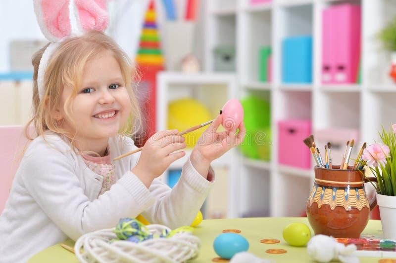 Ragazza felice con le orecchie del coniglietto che si prepara per Pasqua immagini stock libere da diritti