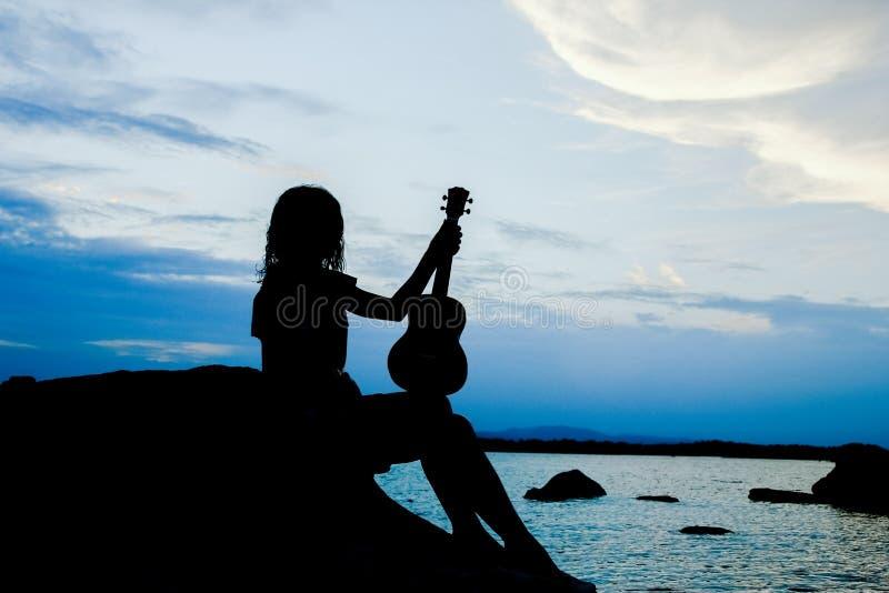 Ragazza felice con le ukulele dal mare sul fondo della siluetta della natura fotografie stock libere da diritti