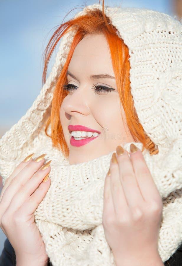 Ragazza felice dai capelli rossi del ritratto in sciarpa bianca calda all'aperto fotografia stock
