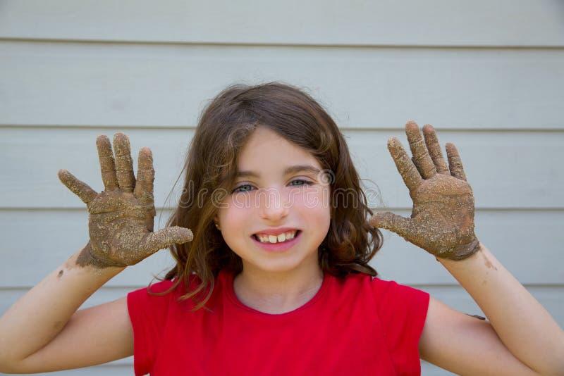 Ragazza felice del bambino che gioca con il fango con sorridere sporco delle mani fotografie stock
