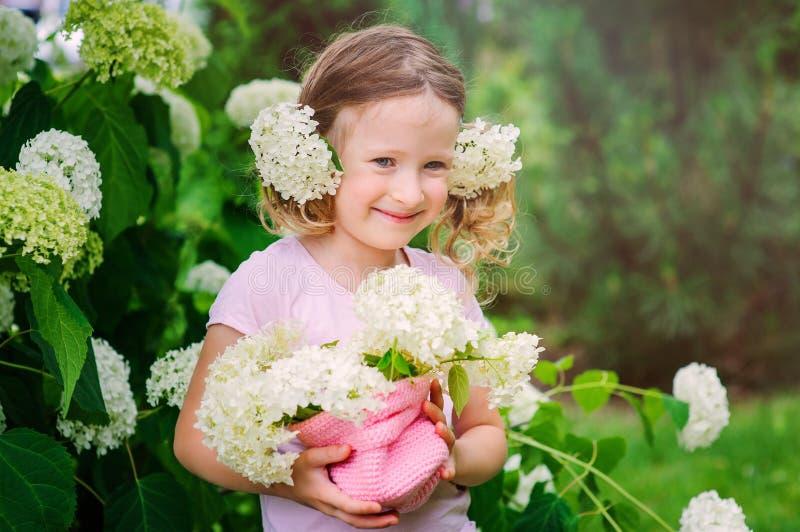 Ragazza felice del bambino che gioca con il mazzo dell'ortensia nel giardino di estate immagini stock libere da diritti