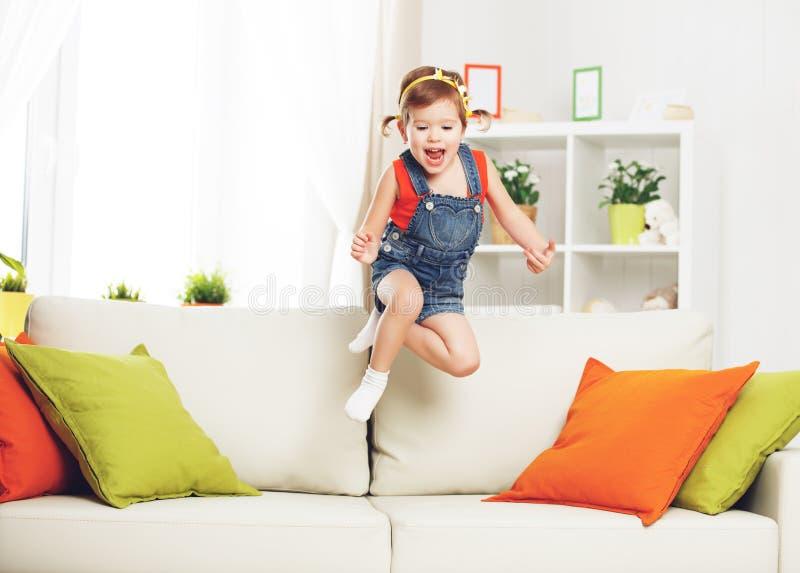 Ragazza felice del bambino che gioca e che salta sullo strato a casa fotografie stock libere da diritti