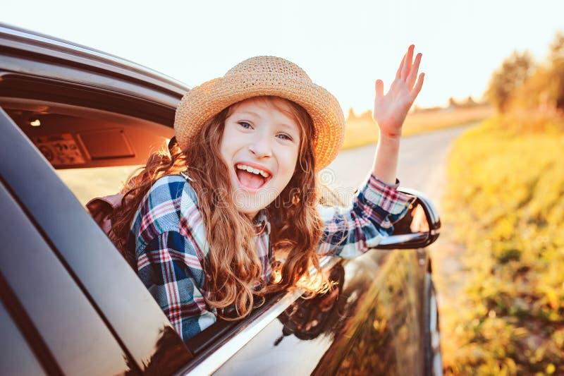 Ragazza felice del bambino che guarda fuori la finestra di automobile durante il viaggio stradale sulle vacanze estive immagini stock libere da diritti