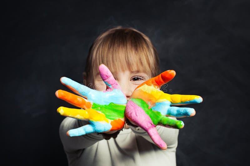 Ragazza felice del bambino che mostra le sue mani di verniciatura variopinte sul ritratto del fondo della lavagna dell'aula immagine stock libera da diritti