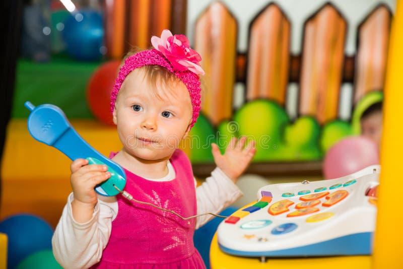 Ragazza felice del bambino che parla sul telefono sul campo da giuoco fotografia stock libera da diritti