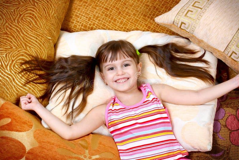 Ragazza felice del bambino che riposa sul cuscino molle fotografia stock libera da diritti