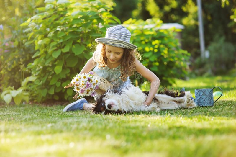 Ragazza felice del bambino che si rilassa nel giardino di estate con il suoi cane dello spaniel, cappello d'uso del giardiniere e fotografia stock libera da diritti