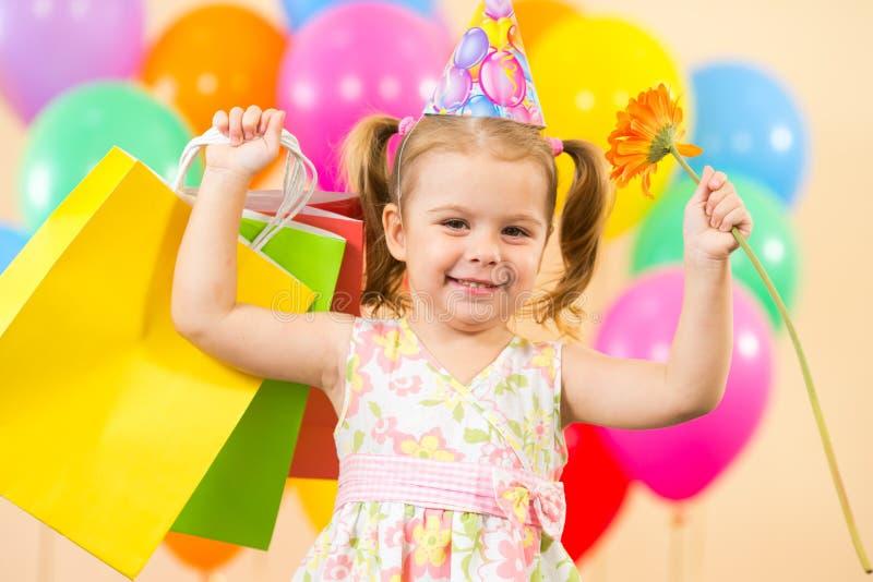 Ragazza felice del bambino con gli aerostati, regali sul compleanno fotografie stock libere da diritti