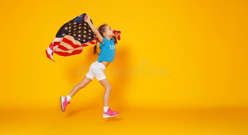 Ragazza felice del bambino con la bandiera degli Stati Uniti d'America U.S.A. su fondo giallo fotografia stock libera da diritti
